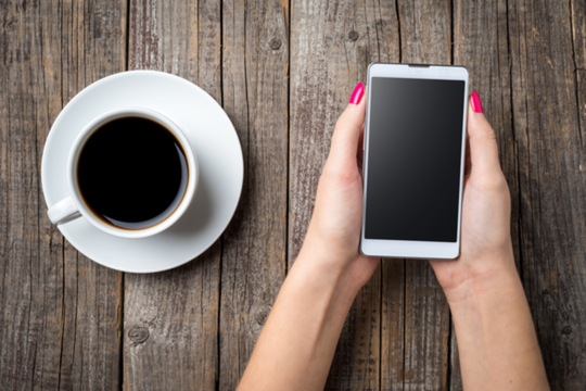 coffee cup and woman holding cell phone