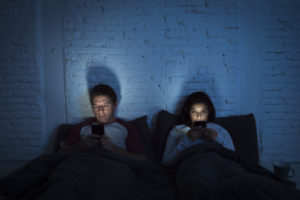 couple in bed with mobile phone screens illuminating faces