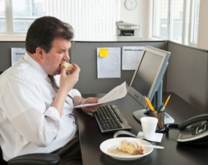 Office worker eating sitting at desk in cubicle