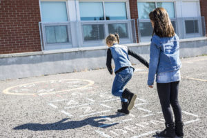 Two girls playing hopscotch on playground