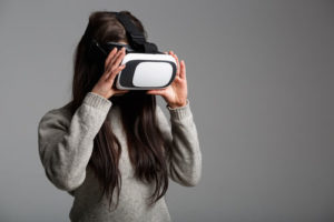 woman with long brown hair wearing virtual reality goggles