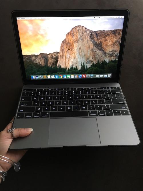 One handing holding Macbook