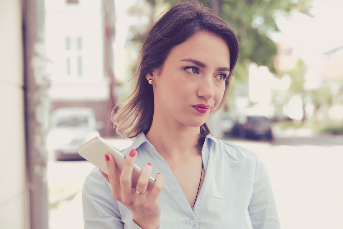woman looking annoyed away from phone