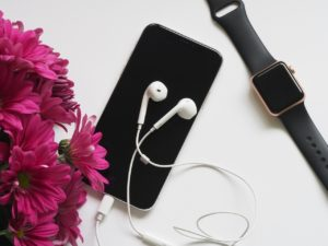 iPhone with earbuds flowers and Apple Watch