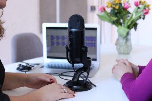 women podcasting with laptop and mic