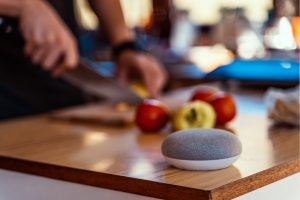 man chopping vegetables with google home