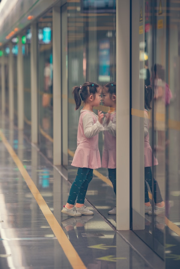 Toddler girl leaning on glass reflective door